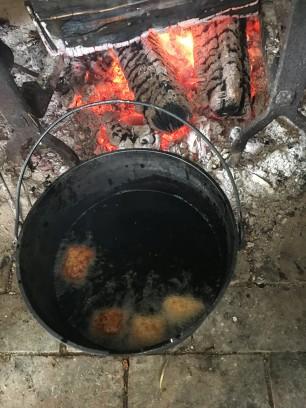 Doughnuts frying in kettle of lard